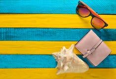 Accesorios femeninos de la playa en un fondo de madera amarillo azul concepto del recorrido Shell, vidrios, monedero Endecha plan Fotos de archivo