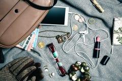 Accesorios femeninos del bolso femenino sobre fondo gris Imágenes de archivo libres de regalías