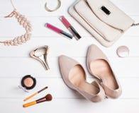 Accesorios femeninos del color beige en la tabla de madera blanca Fotografía de archivo libre de regalías