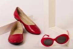 Accesorios femeninos del color rojo - zapatos y gafas de sol en una pizca Imagen de archivo