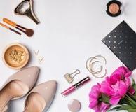 Accesorios femeninos elegantes, cosméticos y peonías rosadas en Imagenes de archivo