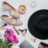 Accesorios femeninos elegantes y peonías rosadas en el backgroun blanco Imagen de archivo libre de regalías