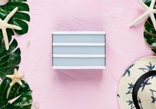 Accesorios femeninos en fondo rosado con el sombrero elegante blanco de la moda, cáscaras, hojas tropicales del monstera, estrell imagen de archivo libre de regalías