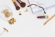 Accesorios femeninos hermosos del color oro en la tabla blanca Fotografía de archivo