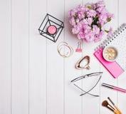 Accesorios femeninos lindos y flores rosadas en la tabla Fotos de archivo libres de regalías