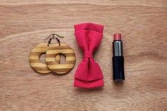 Accesorios femeninos pendientes, corbata de lazo, lápiz labial Imagenes de archivo
