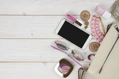 Accesorios femeninos que caen del bolso en fondo de madera con el copyspace Imagen de archivo libre de regalías