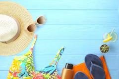Accesorios femeninos sombrero, traje de baño, protección solar, gafas de sol, sombrero, chancletas y endecha del plano de los aur Imágenes de archivo libres de regalías