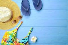 Accesorios femeninos sombrero, traje de baño, protección solar, gafas de sol, sombrero, chancletas y endecha del plano de los aur Imagenes de archivo