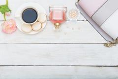 Accesorios femeninos y una taza de café en una parte posterior de madera blanca Imágenes de archivo libres de regalías
