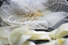 Accesorios hermosos de los ornamentos del blanco y de la leche para las muchachas, el sombrero con una pluma y las cintas de saté Fotografía de archivo libre de regalías