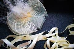 Accesorios hermosos de los ornamentos del blanco y de la leche para las muchachas, el sombrero con una pluma y las cintas de saté Foto de archivo
