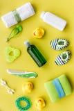 Accesorios, juguetes, toalla y ropa del cuidado del bebé en la opinión superior del fondo amarillo Imágenes de archivo libres de regalías