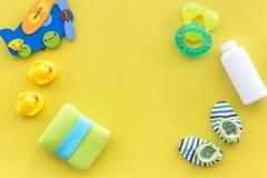 Accesorios, juguetes y ropa del cuidado del bebé en mofa amarilla de la opinión superior del fondo para arriba Imagen de archivo