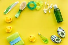 Accesorios, juguetes y ropa del cuidado del bebé en mofa amarilla de la opinión superior del fondo para arriba Fotos de archivo