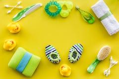 Accesorios, juguetes y ropa del cuidado del bebé en mofa amarilla de la opinión superior del fondo para arriba Fotos de archivo libres de regalías