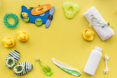 Accesorios, juguetes y ropa del cuidado del bebé en mofa amarilla de la opinión superior del fondo para arriba Fotografía de archivo