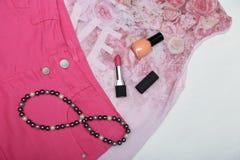 Accesorios lápiz labial, esmalte de uñas y collar de la muchacha en la ropa rosada Imagenes de archivo