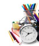 Accesorios, libros y reloj de alarma de la escuela. Fotos de archivo