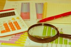 Accesorios lupa del negocio, calculadora, pluma y gráficos, tablas, cartas en un escritorio de oficina de madera imagenes de archivo