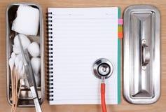 Accesorios médicos con el cuaderno en blanco Foto de archivo libre de regalías
