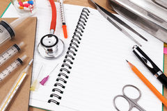 Accesorios médicos con el cuaderno en blanco en la tabla de madera Fotos de archivo