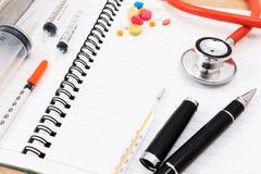 Accesorios médicos con el cuaderno en blanco en la tabla de madera Foto de archivo