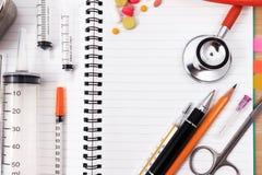 Accesorios médicos con el cuaderno en blanco en la tabla de madera Fotografía de archivo libre de regalías
