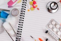 Accesorios médicos con el cuaderno en blanco en la tabla de madera Imagenes de archivo