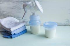 Accesorios manuales de la bomba de lactancia del bebé en la tabla en fondo gris Fotos de archivo libres de regalías