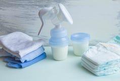 Accesorios manuales de la bomba de lactancia del bebé en la tabla en fondo gris fotografía de archivo