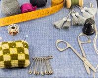 Accesorios maravillosamente presentados para la costura en un fondo de los vaqueros Foto de archivo libre de regalías