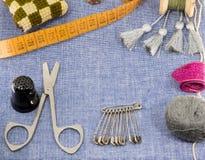 Accesorios maravillosamente presentados para la costura en un fondo de los vaqueros Imagen de archivo libre de regalías