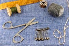 Accesorios maravillosamente presentados para la costura en un fondo de los vaqueros Imagen de archivo