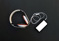 Accesorios musicales en un fondo oscuro Auriculares y smartph Imagen de archivo