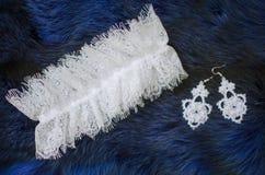 Accesorios nupciales del cordón blanco en el fondo del azul de la piel Weddin Imágenes de archivo libres de regalías