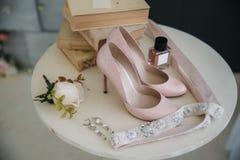 Accesorios nupciales en una silla blanca con las flores, zapatos del perfume concepto de la ropa Imagenes de archivo