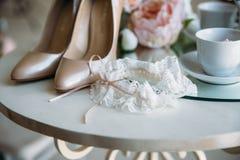 Accesorios nupciales en una silla blanca con las flores, zapatos del perfume concepto de la ropa Fotos de archivo libres de regalías