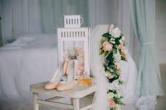 Accesorios nupciales en una silla blanca con las flores, zapatos del perfume concepto de la ropa Imagen de archivo libre de regalías