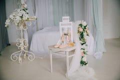 Accesorios nupciales en una silla blanca con las flores, zapatos del perfume concepto de la ropa Imágenes de archivo libres de regalías