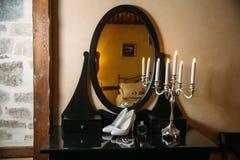 Accesorios nupciales en una silla blanca con las flores, zapatos del perfume en la tabla negra concepto de la ropa Foto de archivo libre de regalías