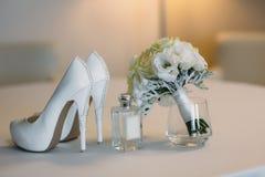 Accesorios nupciales en una silla blanca con las flores, zapatos del perfume, ramo concepto de la ropa Foto de archivo libre de regalías