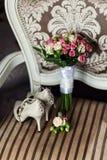 Accesorios nupciales tales como zapatos, mentira del ramo en una silla Imagenes de archivo