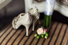 Accesorios nupciales tales como zapatos, mentira del ramo en una silla Fotografía de archivo