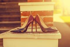 Accesorios nupciales - zapatos de la novia del color de Burdeos en railin de la escalera Fotografía de archivo libre de regalías