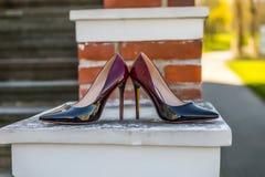 Accesorios nupciales - zapatos de la novia del color de Burdeos en railin de la escalera Fotos de archivo