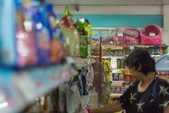 Accesorios o alimento para animales de las compras de la mujer en petshop Foto de archivo