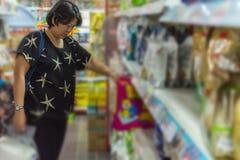 Accesorios o alimento para animales de las compras de la mujer en petshop Imagen de archivo