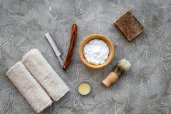 Accesorios para afeitar Brocha de afeitar, maquinilla de afeitar, espuma en la opinión superior del fondo de piedra gris de la ta Fotografía de archivo