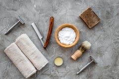 Accesorios para afeitar Brocha de afeitar, maquinilla de afeitar, espuma en la opinión superior del fondo de piedra gris de la ta Imágenes de archivo libres de regalías